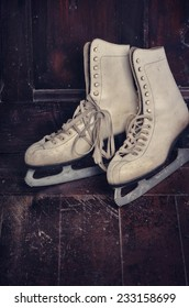 White ice skates on rustic wooden background