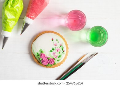 White icing cookie with painted roses on white background and cornets with glaze for painting