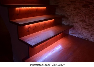 White illuminated wooden stairs and rough stone wall