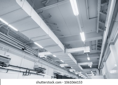 White Industrial Air duct from air conditioner cooling pipe with plumbing at ceiling in large industrial hall.