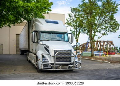 White industrial big rig long haul semi truck tractor with grille guard and refrigerator semi trailer unloading commercial cargo standing at warehouse building dock gate at industrial area