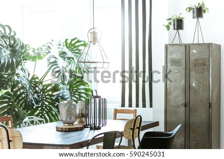 White, industrial dining room with metal wardrobe and wood table