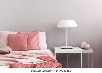 White industrial lamp on simple nightstand table next to cozy bed with pink bedding