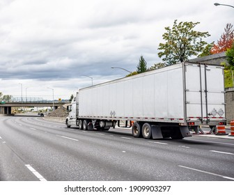 White industrial long haul big rig semi truck with high cabin transporting commercial cargo in dry van semi trailer driving on the wide interstate highway road with bridge and trees on the side