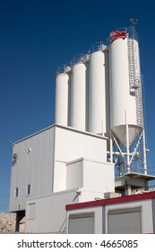 white industrial silos against a clear blue sky