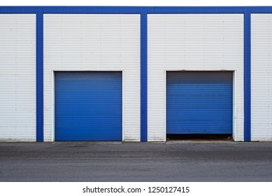 White Industrial warehouse with blue door for trucks.