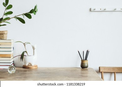 The white interior with copy space, books, vintage accessories and leafs. Minimalistic concept of home interior.