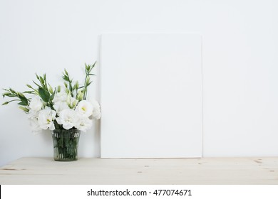 White interior decor, fresh natural flowers in vase and canvas