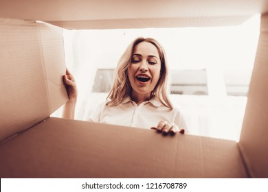 White Interior. Smiling Girl. Master with Woman in Apartment. Paper Brown Box. Woman Looks into Empty Box. Girl Looks in Box. Woman Opens Big Postal Parcel. Postal Box. Happy Blond Famale.