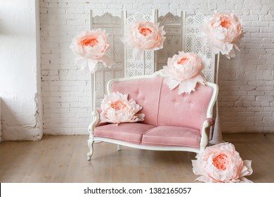 White interior with sofa with pretty pink fabric upholstery in a room with wooden floor and white walls. And big paper flowers around it