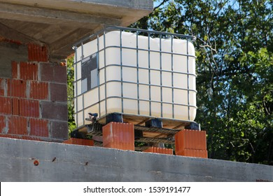 White intermediate bulk container or IBC plastic tank with metal cage put on top of red building blocks at local construction site surrounded with unfinished family house wall and dense tree
