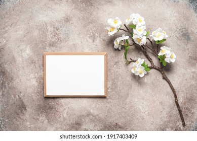 White invitation card mockup with cherry blossom branch artificial . Beige grunge background. Spring stationery scene. Top view, flat lay