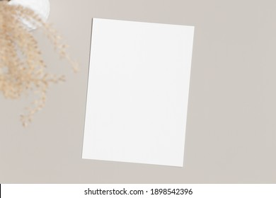 White invitation card mockup with a dried grass on a beige table. 5x7 ratio, similar to A6, A5.