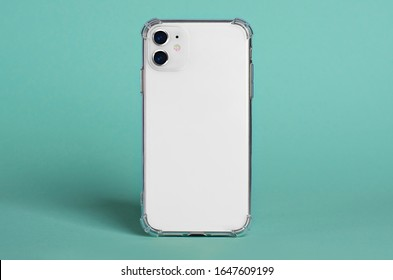 White iPhone 11 in clear silicone case back view isolated on green background, phone case mock up iPhone 12