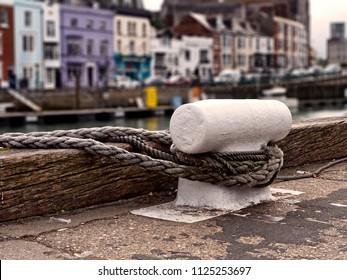 White iron bollard with ropes