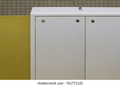 White iron locker in front of yellow wall and mosaic wall background.