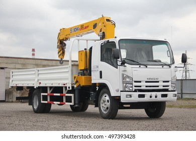 A White Isuzu flatbed truck with yellow crane arm is in the parking lot against a gray cloudy sky - Russia, Moscow, 30 September 2016