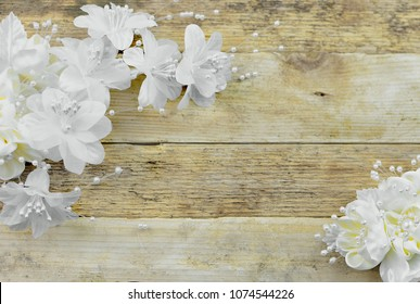 White and ivory silk flowers on a rustic wooden white washed background. Good for wedding or anniversary.Copy space
