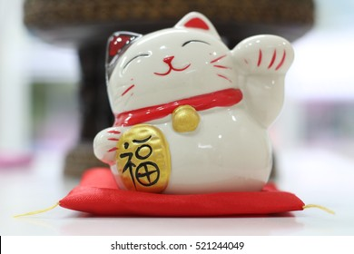 A white Japanese figurine cat beckoning with left upright paw,  made of ceramic wearing red neckerchief with bell and holding gold coin with Japanese letters read (??? senmanry?) worth ten million ry?