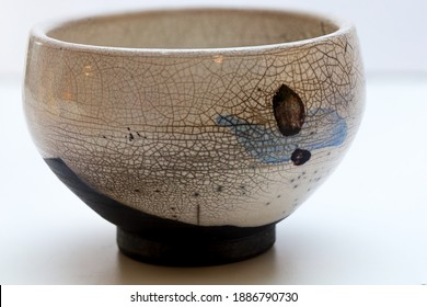 A white Japanese style bowl with abstract decoration and crackle glaze