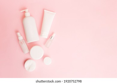 White jars of cosmetics on a pink pastel background. Bath accessories. Face and body care concept. Copy space, flat lay