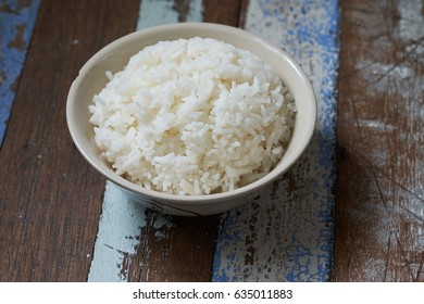 White jasmine rice bowl on wooden table. Main meal of thai people, a lot of carbohydrate.