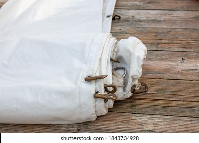 A white jib sail rolled up on the dock with shows a close up of the bolt rope and copper hanks sewn onto the sail.