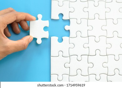 White jigsaw in the hands, The correct solution. Teamwork, Solving and completing the task. Last piece of jigsaw puzzle. Assembling  jigsaw puzzle pieces.