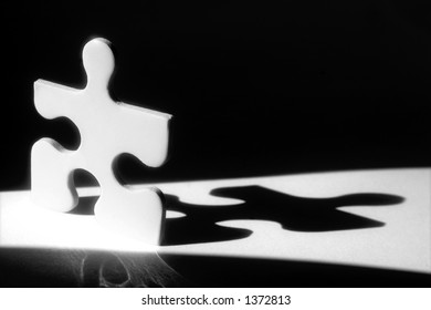White jigsaw piece in beam of light with shadow behind