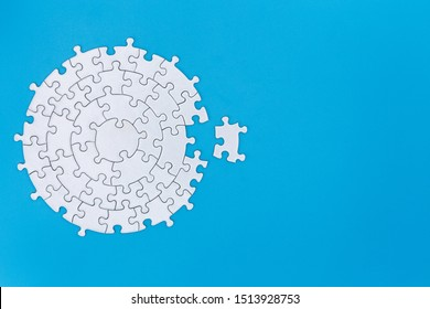 White jigsaw pieces on a blue background, Copy space, Jigsaw puzzle with missing piece. Completing final task.