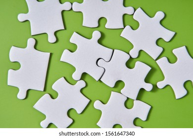 lot of white jigsaw puzzle on the green background