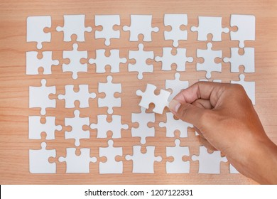 White jigsaw puzzle on wood table.