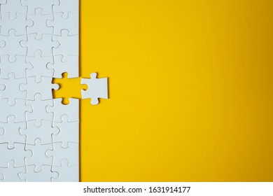 White jigsaw puzzle on yellow background. Team business success partnership or teamwork