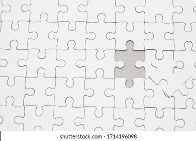 White jigsaw puzzle pattern background. placing last piece of jigsaw puzzle