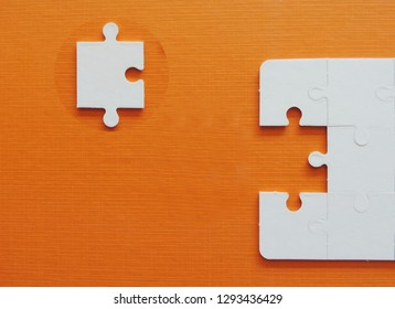 White jigsaw puzzle pieces on an orange background.
