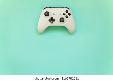 White joystick gamepad, game console on blue colourful trendy modern fashion pin-up background. Computer gaming competition videogame control confrontation concept