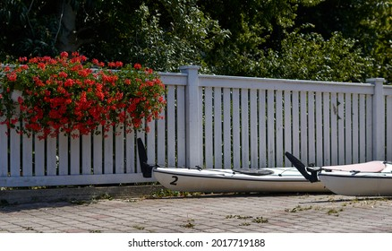 white kayaks on the background of a white wooden fence, pots with flowers on the fence . High quality photo