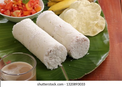 White Kerala style Puttu on Banana leaf with pappadam,banana, tomato curry with wooden base