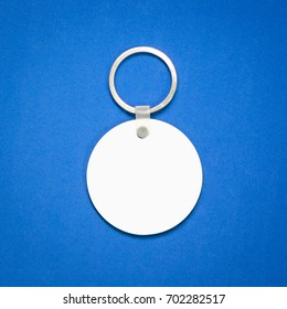 White key ring on blue background. Key chain for your design. Hanging accessory or souvenir. ( Circle shape )