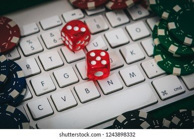 White keyboard with some red dices and poker chips on a green poker table. Gambling online addiction concept. Play poker on internet and win money.