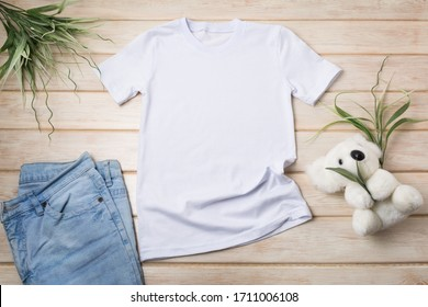 White kids cotton T-shirt mockup with koala bear soft toy and blue jeans. Design t shirt template, tee print presentation mock up - Shutterstock ID 1711006108