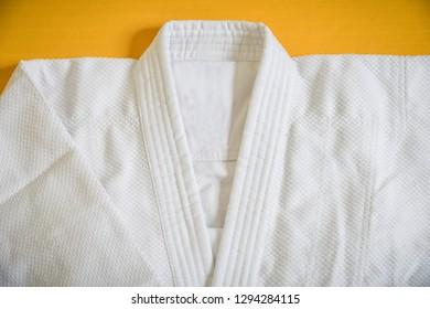 white kimono for sambo, judo, jujitsu posing on mat.