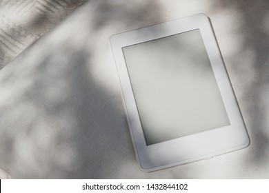 White kindle / e-reader laying on a white pillow with tree shadow and sun rays