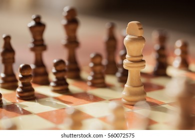 White king on a chess board alone against all black pieces. White king fights against black enemy team on board.