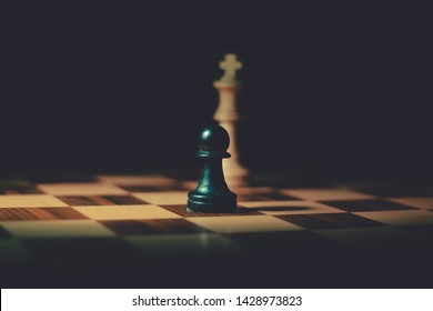 A white king piece coming from shadows behind a black pawn