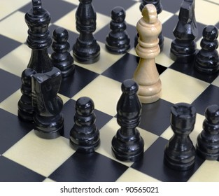 white king surrounded by the black team on a chessboard