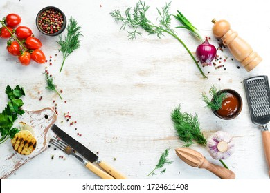 White kitchen background. Kitchen board, vegetables and spices on a white wooden background. Top view.