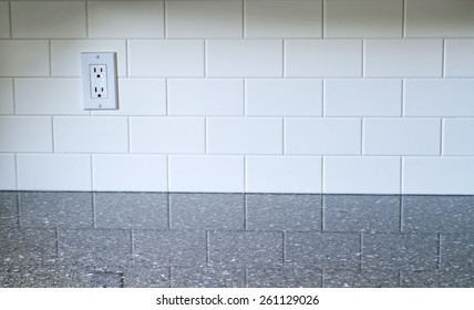 White Kitchen backsplash with a white outlet on the left side with quartz countertop