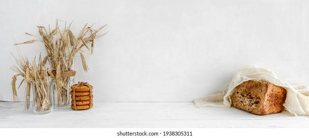 Pancarta blanca de la cocina - galletas de avena, pan de grano y orejas de grano sobre una mesa blanca.
