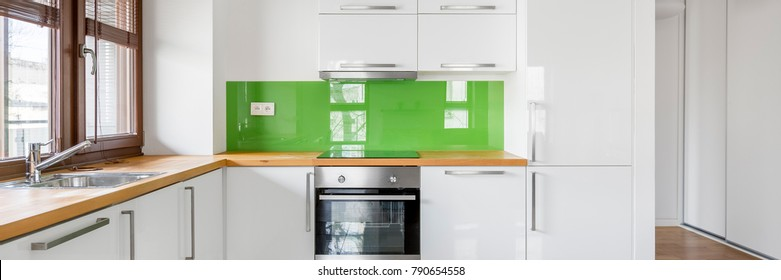 White kitchen with big window, wooden countertop and green backsplash, panorama